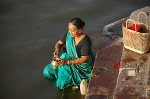 Woman Placing Ashes into Ganges River