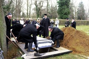 Family Lowering Casket into Grave